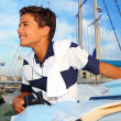 Boy teen sailorsitting on marina boat chart map - Stock Photo