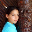 Latin mexican teen girl smile indian wood totem — Stock Photo