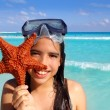 Latin tourist girl holding starfish tropical beach - Stok fotoğraf