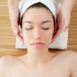 Beautiful woman face massage with white towel — Stock Photo #5495529