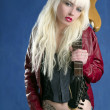 Blond sexy fashion young girl electric guitar rock star blue background — Stock Photo
