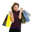 Shopaholic woman with colorful bags over white — Stock Photo