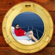 Royalty-Free Stock Photo: Man relaxed on bean bag over blue sea, round window