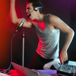 Dj with colorful light and music mixing equipment — Stock Photo