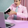 Businessman young shooting handgun computer — Stock Photo