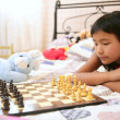 Asian little girl playing chess with teddy rabbit — Stock Photo #5496980