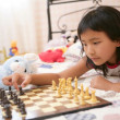 Asian little girl playing chess with teddy rabbit — Stock Photo