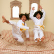 Two little asian judo gils jump on sofa - Stock Photo