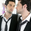 Handsome narcissistic young man looking in a mirror — Stock Photo