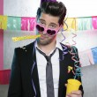 Blowing noisemaker suit party funny young man — Stock Photo #5497441