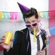 Blowing noisemaker suit party funny young man - Stock Photo