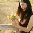 Beautiful woman in golden outdoor, yellow flower — Stock Photo #5498016