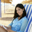Beautiful woman with a book relaxed on the beach — Foto de stock #5498063