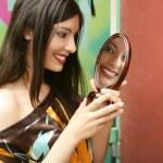 Beautiful woman looking in mirror — Stock Photo
