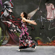 Elegant fashion woman running over urban graffiti - Stock Photo