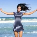 mooie zomerse brunette meisje springen op het strand — Stockfoto