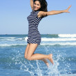 Beautiful summer brunette girl jumping on the beach — Foto Stock
