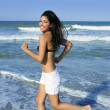 Beautiful summer brunette girl jumping on the beach — Lizenzfreies Foto