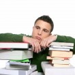 Young unhappy student with stacked books — Stock Photo