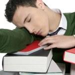 Boy student sleeping over stack books over desk — Stock Photo