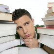 Young unhappy student with stacked books — Stock Photo #5498889