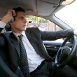 Young suit businessman inside his car - Stock Photo
