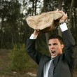 Angry businessman outdoor, big stone in hands - Stok fotoraf