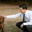 Businessman with dog outdoor in park — Stock Photo #5499210