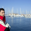 Handsome boy on harbor with red marine coat — Stock Photo