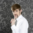 Silence finger gesture retro businessman on wallpaper — Stock Photo