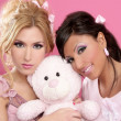 Blonde and brunette girls hug a pink teddy bear - Stock Photo