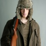 Hunter man fur winter hat holding rifle gun — Stock Photo