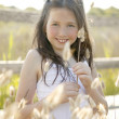Girl at the park playing with flower spike — Stock Photo #5499938