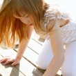 Little girl playing on park wooden floor - Foto Stock