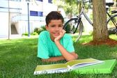Boy teen studying laying green grass garden — Stock Photo