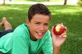 Adolescent garçon mange pomme rouge sur l'herbe jardin — Photo