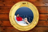 Man relaxed on bean bag over blue sea, round window — Stock Photo