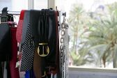 Rack of clothes with fashion accesories, belts — Stock Photo