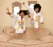 Two little asian judo gils jump on sofa — Stock Photo