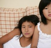 Asian sisters posing portrait on the sofa — Стоковое фото