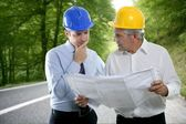 Engineer architect two expertise plan hardhat forest road — Stock Photo