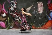 Elegant fashion woman running over urban graffiti — Stock Photo