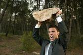 Homme d'affaires en colère extérieure, grosse pierre en mains — Photo