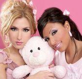 Blonde and brunette girls hug a pink teddy bear — Stock Photo