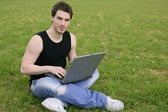 Student young man laptop computer on meadow — Stock Photo