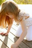 Little girl playing on park wooden floor — Stock Photo