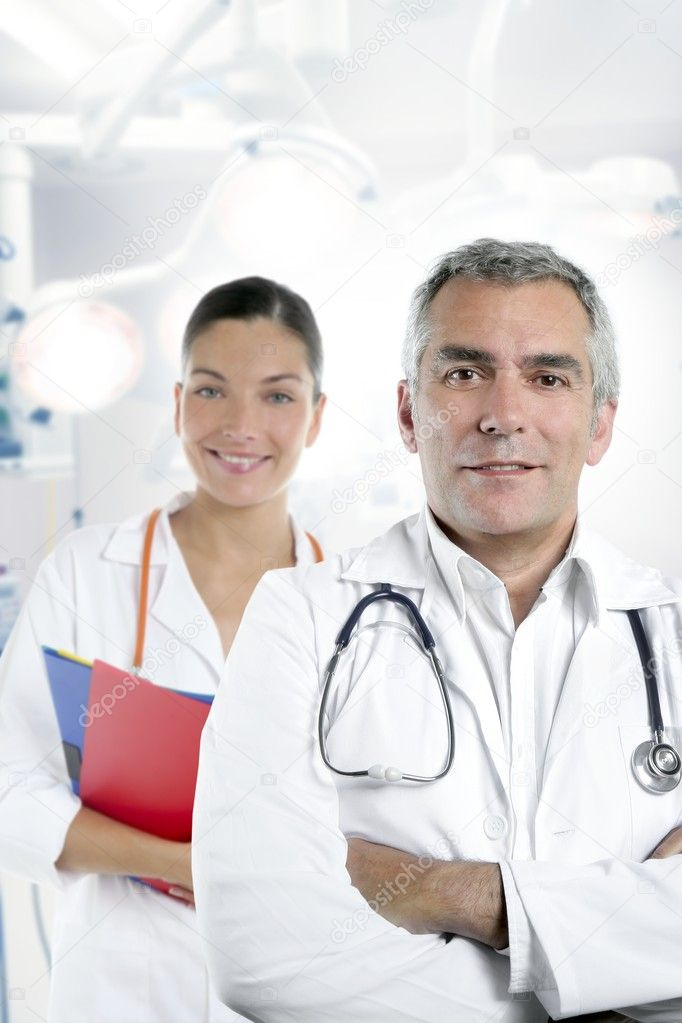 Expertise gray hair doctor beautiful nurse in hospital white corridor — Stockfoto #5494881