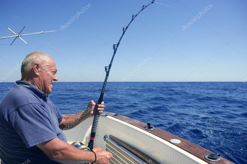 Angler elderly big game sport fishing boat blue summer sea sky — Stock Photo #5496620