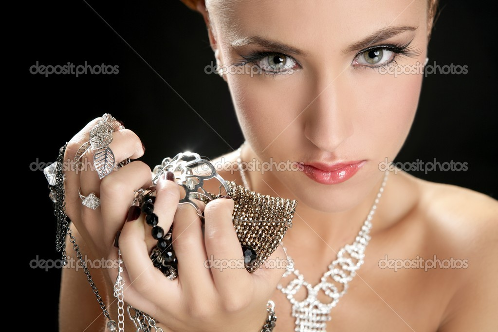 Ambition and greed in fashion woman with jewelry in hands on black background — Stock Photo #5499426