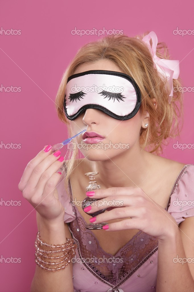 Blond woman smelling perfume sleep mask blind pink background — Photo #5499645